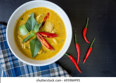 Green curry with chicken on dark wooden table top view. The popular food in Thailand.Thai food flat lay with copy space.