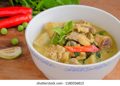 Green curry with chicken on wooden table and vegetable