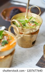 Green curry. A chicken green curry is a very popular Thai food. A green curry is served in a classic brass hot pot, using candle underneath makes it warm last longer. Jasberry rice on the background.