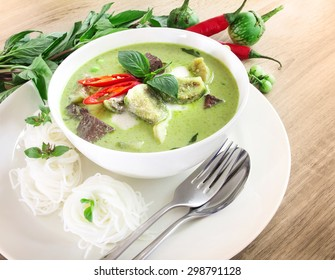 Green curry creamy coconut milk with chicken with thai rice noodle , the Popular Thai food called Kanom jeen , Gaeng Keow Wan Gai on wooden table