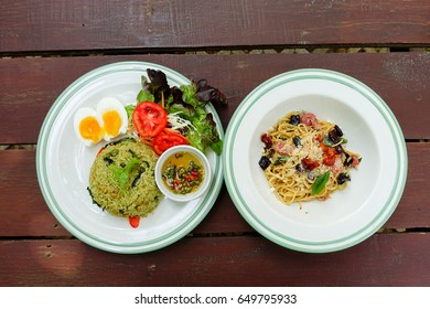 Green curry fried rice and Spaghetti on wooden table.