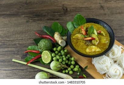 Green curry (Kaeng kheiyw hwan) with Thai food for steamed rice or rice noodles. chicken green curry is thai food very popular on dark wooden background. top view