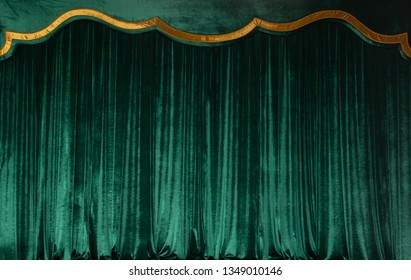 Green curtain of luxurious velvet on the theater stage. Copy space. The concept of music and theatrical art.