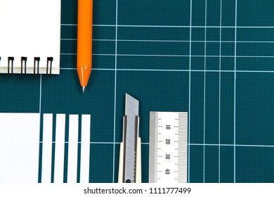 green cutting mat board, cuter knife, notes, pen, paper, ruler stainless. Workspace concept with copy space.