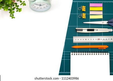 green cutting mat board and flowerpot, table clock on white background.cuter knife, notes, pen, sticky notes, office clips, ruler stainles.office items for Workplace concept.top view with copy space.