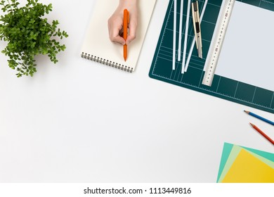 green cutting mat board, flowerpot,cuter knife,color paper, pencil on white background.Workplace concept. top view with copy space. a female hands hold the pen on an empty notebook.Business creation.