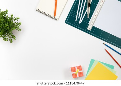 green cutting mat board, flowerpot,minimal gift box,cuter knife,color paper,pencil on white background.Workplace concept.top view with copy space.Business creation.
