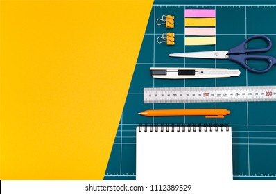 green cutting mat board on yellow background. cuter knife, empty notes, pen, sticky notes, office clips, ruler stainles. soffice items for Workplace concept. top view with copy space.