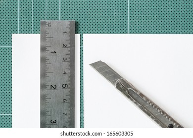 Green cutting mats withi iron ruler and cuter isolated on white background