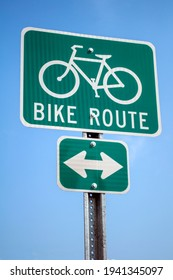 Green cyclist route traffic sign on blue sky.