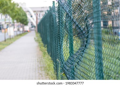 Green damaged wire-mesh fence is ruined after collision with car accident as crushed fence for car insurance and property insurance and loses security and safety with vandalism and barrier demolition