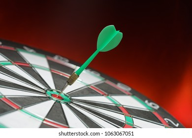 Green dart arrow hitting in the target center of dartboard with red light and black background. Target business, achieve and victory concept .
