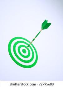 A green dart on an abstract dartboard