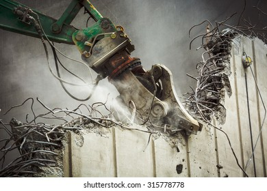 Green demolition excavator takes down concrete wall - close up 3