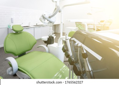 Green dental chair and equipment. Patient reception room in a modern medical center. Toned