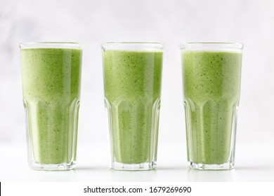 Green detox juice on white marble background with copy space. Vegan detox concept.