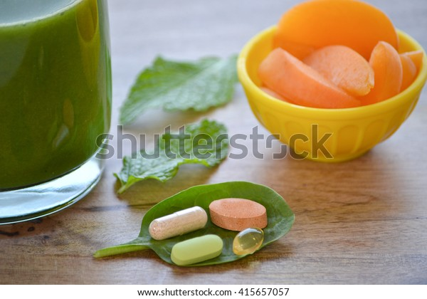 Green detox smoothie, dietary supplements and a serving of apricots on wooden table