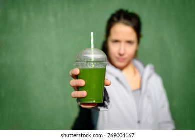 Green detox smoothie. Sporty woman offering nutritive vegetable drink. Fitness diet and healthy lifestyle concept.