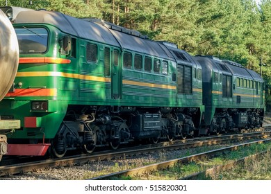 Green diesel cargo locomotive in forest