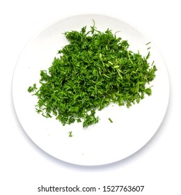Green dill sliced in small pieces on a white dish on a white background.