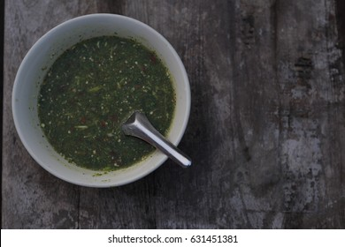 Green dip in a cup on a wooden floor.