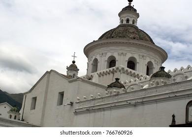 Green dome on top of a white colonial era church in Quito, Ecuador