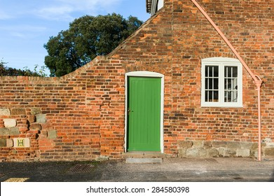 Green door in bricked wall.
