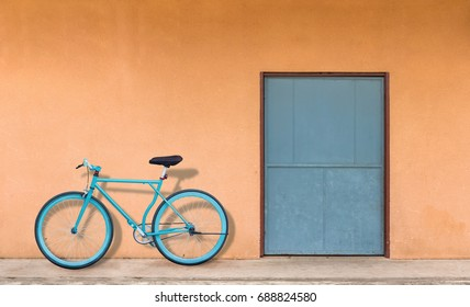 The green door and the orange wall have a parked bicycle against the wall.