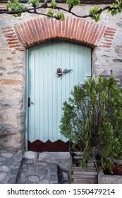 Green door to rustic stone house