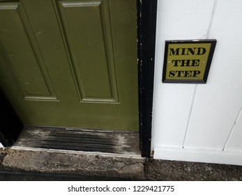 green door with white wall and mind the step sign