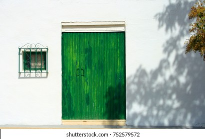 Green door and window on white wall in Pedrera, Andalusia, Spain