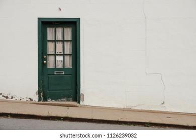 Green doors on white facade and steep sidewalk.