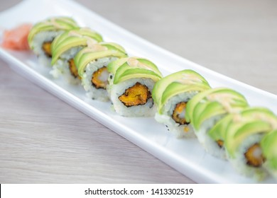 Green dragon sushi roll with eel, avocado, cucumber and ginger, accompanied with fried tempura shrimp. Traditional asian rice sushi healthy seafood. White plate isolated background.