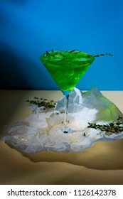 A green drink with ice cubes and green branches in a glass for mojito on crumpled wrapping paper on yellow table and blue background whth shadows. Conceptual and advertising design. Copy space.