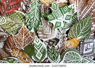 A lot of green and dry patterned leaves close up. Autumnal background.
