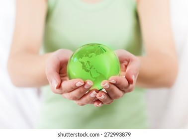 Green Earth Globe Protected by human hands. Glass globe in female hand.Sustainable development for the future of the our planet.