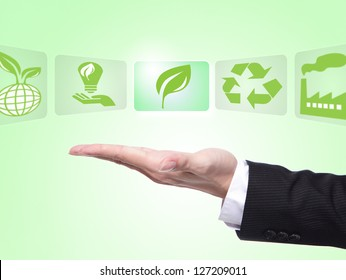green eco icons concept , business man hand palm holding all kinds of icon about eco with green background