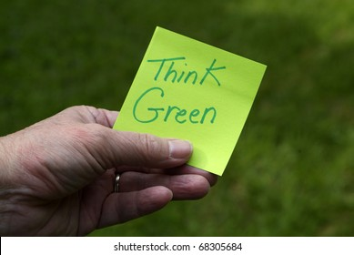 """Green Eco Innovation sustainability concept: Person holding green sticky note with """"Think Green"""" written on it"""