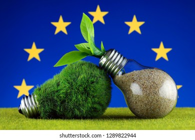 Green eco light bulb with grass, plant growing inside the light bulb, and European Union Flag. Renewable energy. Electricity prices, energy saving in the household.