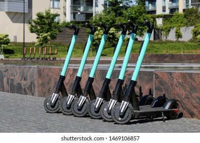Green electric rental scooters by Tier in a row in a park in downtown Helsinki, Finland, June 2019. Scooters rented with phone apps have been a big trend in Helsinki 2019. Color image.