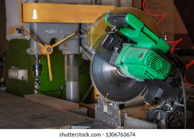 The green electrical circular mitre saw on the carpenter workbench in the workroom. Soft focus.