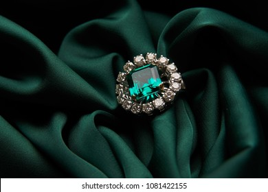 Green emerald fashion engagement diamond ring on green satin background. Luxury female jewellery, close-up. Selective focus