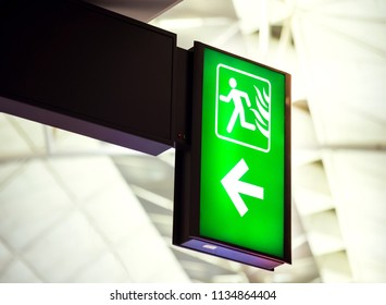Green emergency exit sign in airport.