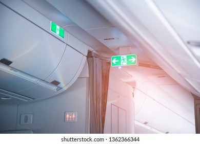 Green Emergency Exit Sign in commercial aircraft cabin.