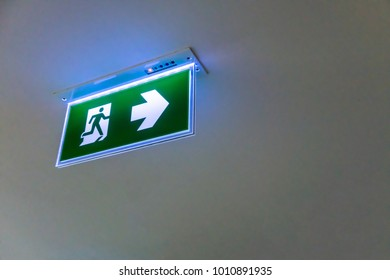 Green emergency exit sign. Direction to the escape way on white background. Perspective view
