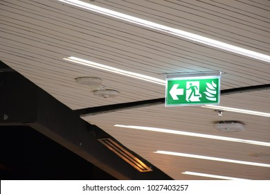 green emergency exit sign in shopping mall.