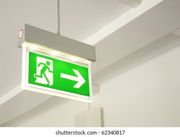 green emergency exit sign showing the way to escape