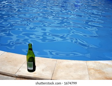 Green empty bottle of beer on the pool border