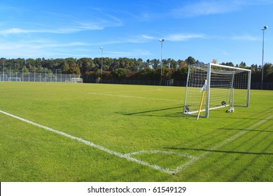 green empty football field with flag and nets