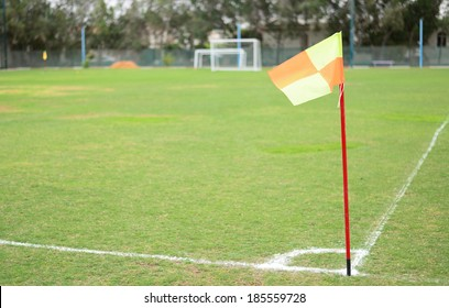 Green empty football field in summer with corner flag